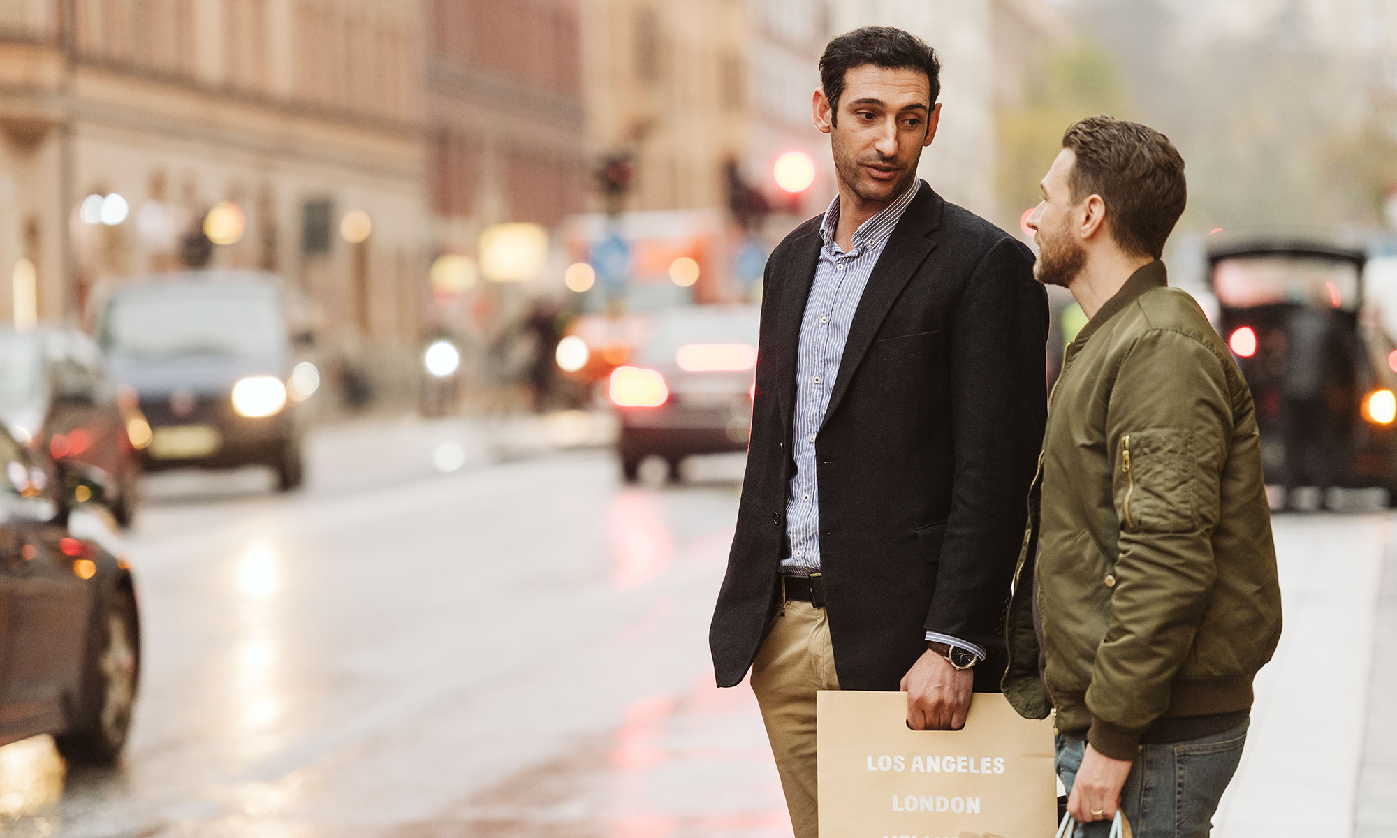Two men with shopping bags in the city.